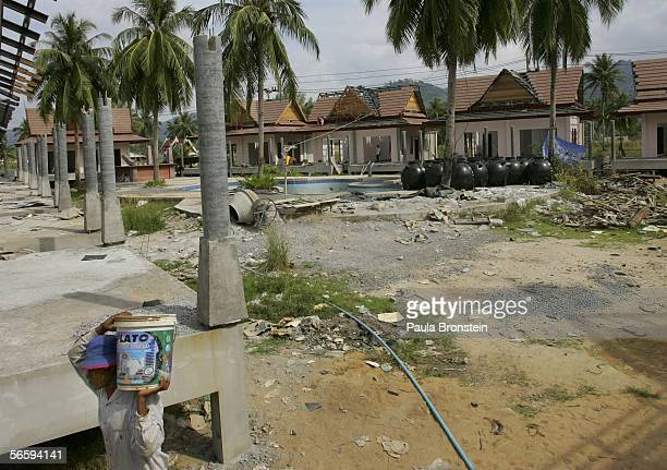 Thai construction worker carries water on a building site for a new hotel along the beach January 13 2006 in Khao Lak Thailand Over a year after the...
