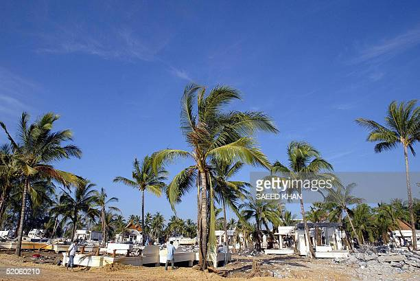 Thai couple walk through the ruins of the devastated Bang Niang beach where rescuers are still in search of missing western tourists on the...