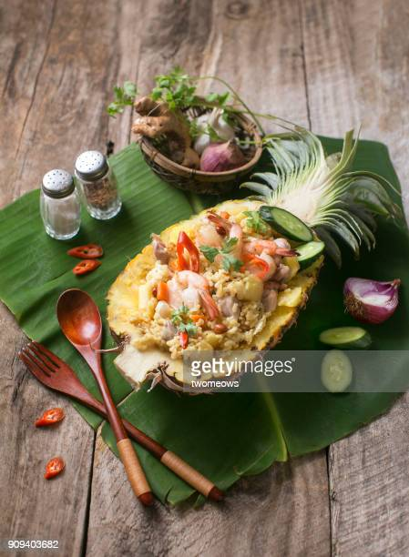 Thai cuisine pineapple fried rice on wooden table top.