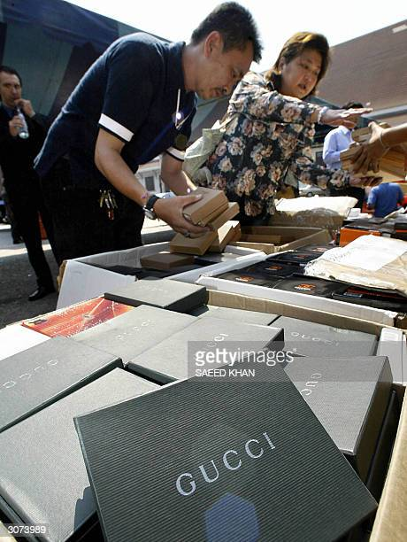 Thai customs officers arrange counterfeit Gucci leather items during a display at the customs house in Bangkok 11 March 2004 Thai authorities...