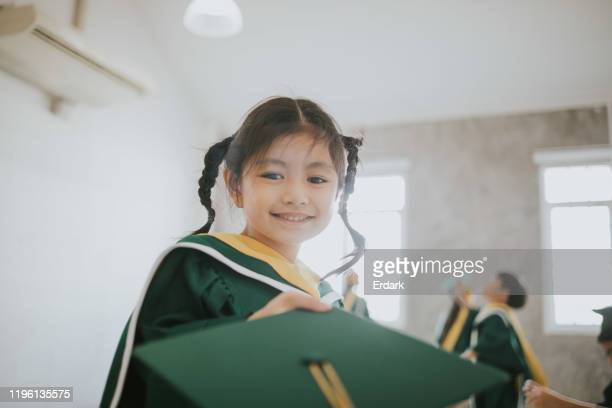 thai cute baby girls receive her graduation hat with graduation day stock photo - alumni stock pictures, royalty-free photos & images
