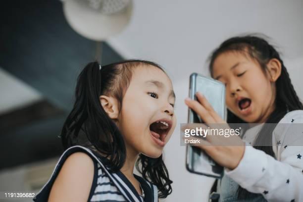 hija linda tailandesa y su amigo disfrutan de hablar videoconferencia a amigo mientras que el uso de teléfono inteligente en casa - 8 9 años fotografías e imágenes de stock