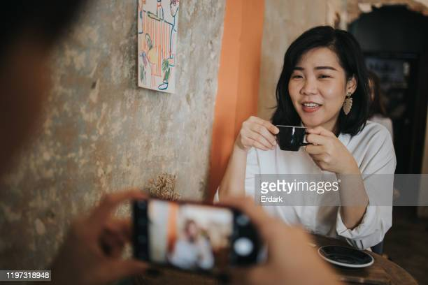 thai designer and her friend taking a break at coffee shop - social media marketing stock pictures, royalty-free photos & images