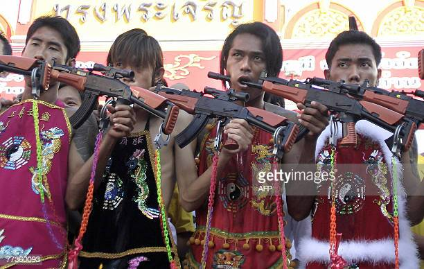 Thai devotees hold toy guns through their pierced cheeks during the vegetarian festival in Phuket island 17 October 2007 The participants are...