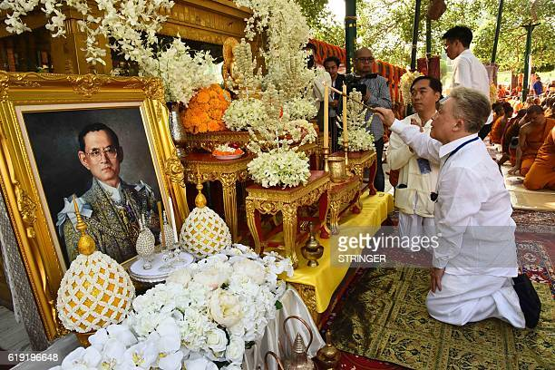 Thai devotees offer special prayers under the sacred Bodhi Tree for the soul of the late Thai King Bhumibol Adulyadej at Bodhgaya on October 30 2016...