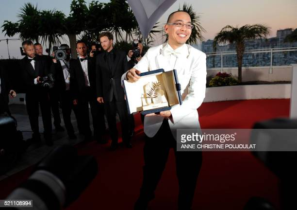 Thai director Apichatpong Weerasethakul poses after receiving the Palme dOr award for his film 'Lung Boonmee Raluek Chat' during the closing ceremony...