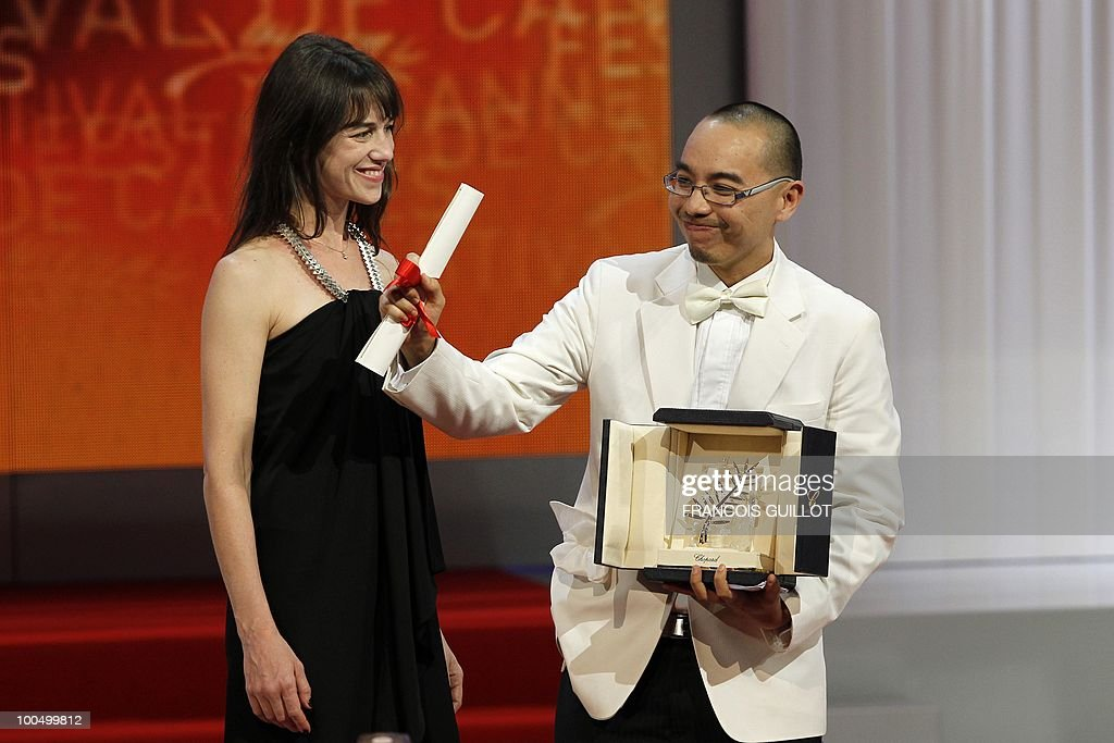 Thai director Apichatpong Weerasethakul poses next to French actress Charlotte Gainsbourg after receiving the Palm d�Or award for his film 'Lung Boonmee Raluek Chat' (Uncle Boonmee Who Can Recall His Past Lives) during the closing ceremony at the 63rd Cannes Film Festival on May 23, 2010 in Cannes.