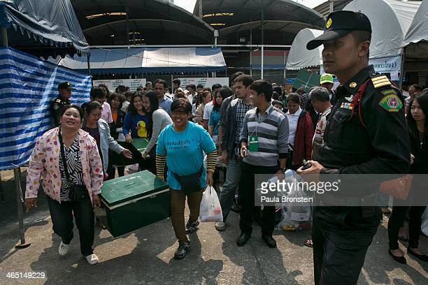 Thai election workers carry ballot boxes as they depart from a closed polling station as advanced voting for the February 2nd general elections was...