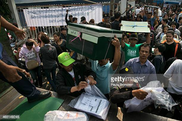 Thai election workers load ballot boxes at a closed polling station as advanced voting for the February 2nd general elections was unable to continue...