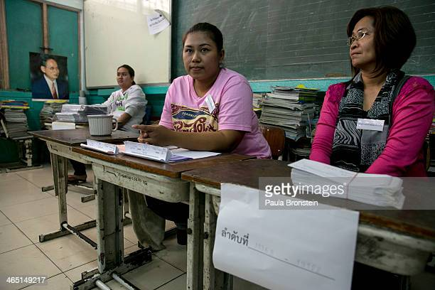 Thai election workers wait for instructions at a recently closed polling station as advanced voting for the February 2nd general elections was unable...