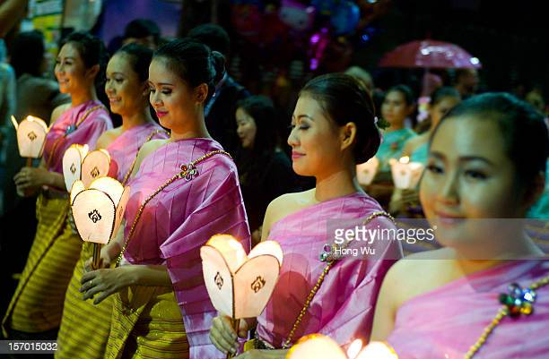 Thai entertainers wear traditional clothes as they parade in the street to celebrate the Yee Peng Festival during the Chiang Mai Yee Peng Lantern...
