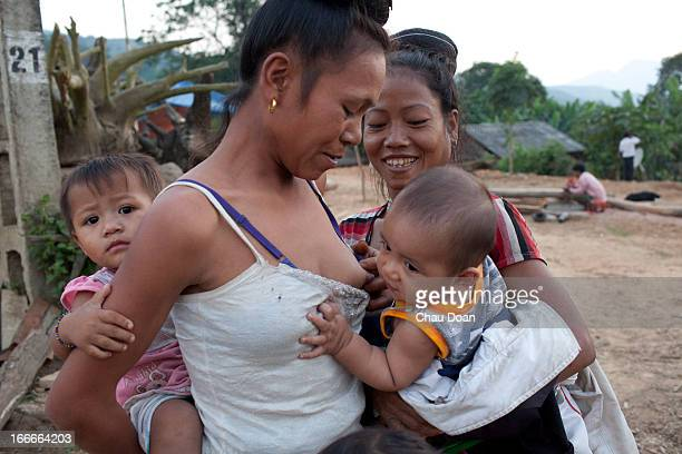 Thai ethnic minority woman breastfeeds her neighbor baby at NaSan 1 village