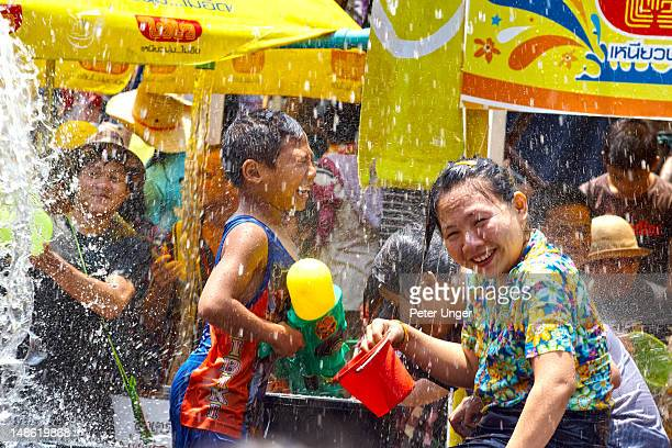 Thai family enjoying getting wet at Songkran Festival.