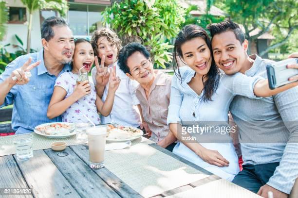 Thai family - grandpa, grandma, mom, dad, daughter and son - having lunch at a terrace. Taking selfies and having fun