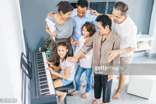 Thai Familienporträt - Opa, Oma, Mama, Papa, Tochter und Sohn. Mädchen spielt Klavier, jeder ist auf sie zu hören. Modernes Interieur