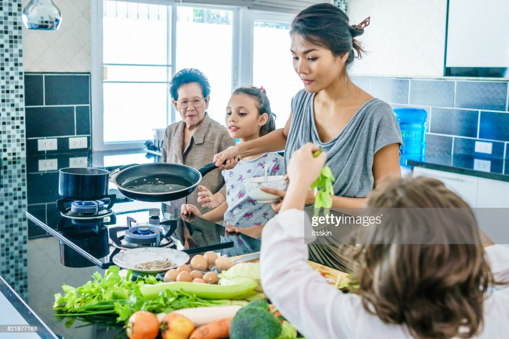 Thai family portrait having fun at the joint cooking. Modern style interior of kitchen. : Stock Photo