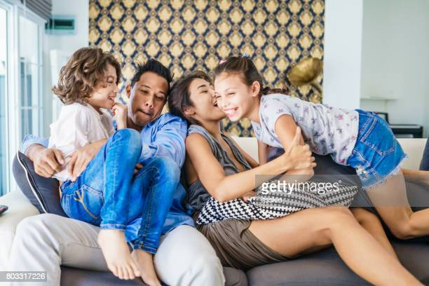 Thai family portrait - mom, dad, daughter and son - sitting on the couch, talk, laugh, enjoing and having fun together. Modern style interior.