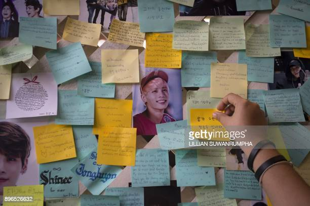 A Thai fan of the late South Korean band SHINee singer Kim JongHyun puts up a note for him during a memorial held by the boyband's Thai fanclub at a...