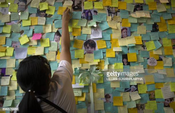 Thai fan of the late South Korean band SHINee singer Kim JongHyun puts up a note for him during a memorial held by the boyband's Thai fanclub at a...