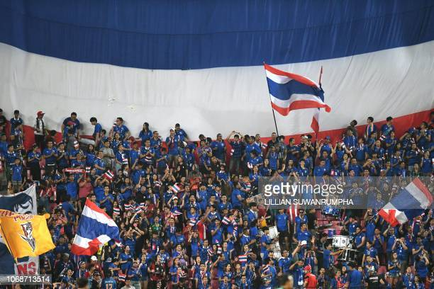 Thai fans cheer in front of a giant flag during the second leg of the AFF Suzuki Cup 2018 semifinal football match between Thailand and Malaysia at...