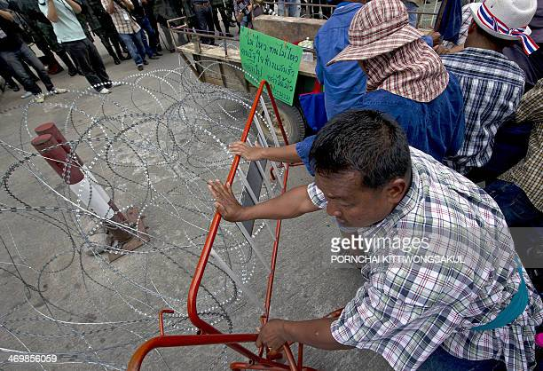 Thai farmers break barbed wire as they protest the government's repeatedly delayed payments for rice submitted to the pledging scheme at the...