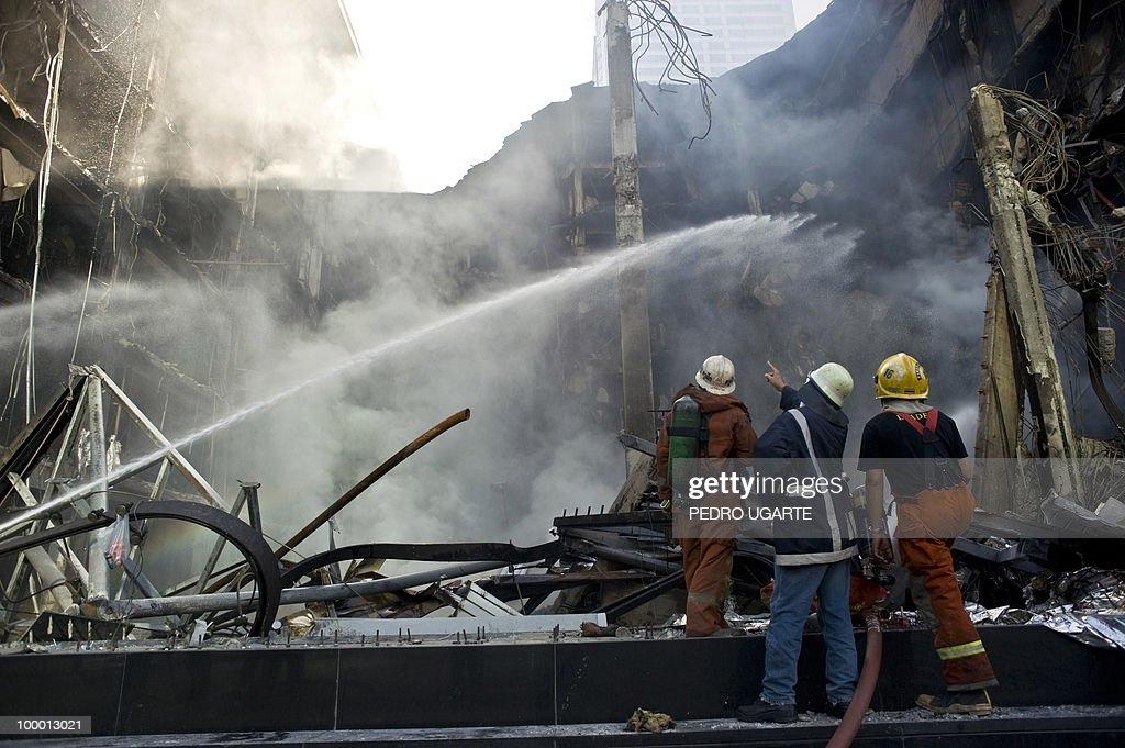 Thai firemen spray hoses on Thailand's biggest shopping mall - Central World - after it was set ablaze the day before following an army assault on an anti-government protest site in downtown Bangkok on May 20, 2010. Thai troops hunted for militant protesters who left parts of Bangkok in flames as the authorities extended a night curfew in the capital despite tentative signs of a return to normality.