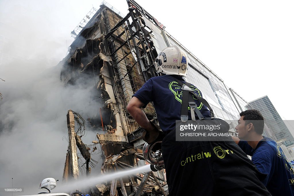 Thai firemen try to douse the flames at Thailand's biggest shopping mall - Central World - after it was set ablaze the day before following an army assault on an anti-government protest site in downtown Bangkok on May 20, 2010. Plumes of smoke hung overhead and gunfire crackled as Bangkok emerged from an curfew aimed at quelling mayhem unleashed by enraged anti-government protesters targeted in an army offensive. AFP PHOTO/Christophe ARCHAMBAULT