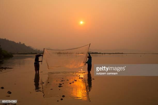 Thai fisherman silhouette in sunrise landscape Mekong river