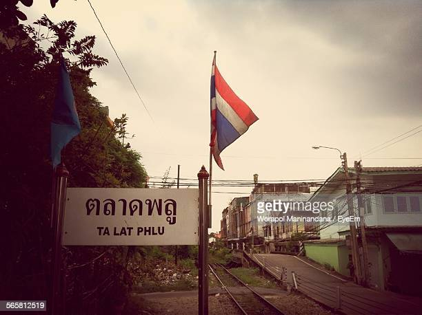 Thai Flag By Railroad Track Against Sky In City