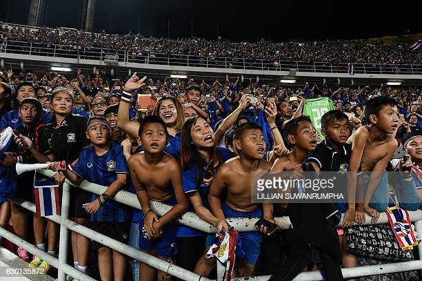 Thai football fans celebrate after Thailand won the AFF Suzuki Cup Final between Thailand and Indonesia at Rajamangala Stadium in Bangkok on December...