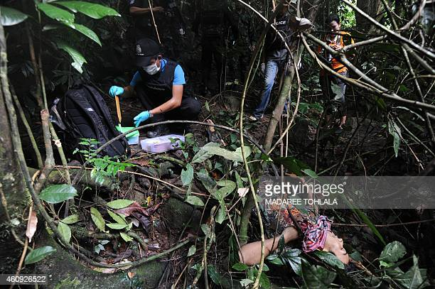 Thai forensic police inspect the body of a suspected separatist militant who was shot dead during a clash with army rangers in the Rangae district of...