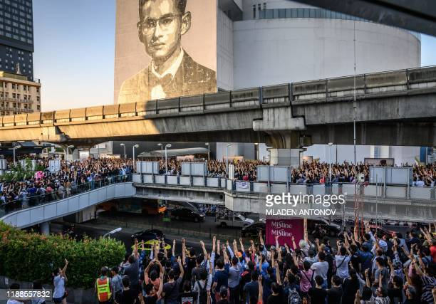 Thai Future Forward Party supporters stand on a skywalk bridge in front of a mural featuring the late Thai King Bhumibol Adulyadej during an...