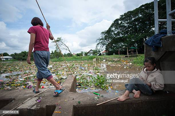Thai girl plays with a smart phone as she waits for her mother who is finding valuables from krathongs on the Ping river after the Loy Krathong...