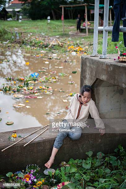 Thai girl waits for her mother on a floodgate while searching for valuables from krathongs in the Ping river after Loy Krathong Festival in Chiang...