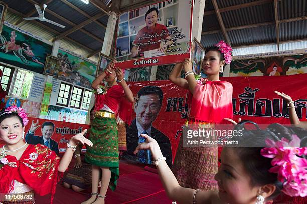 Thai girls in traditional costume carry a picture of ousted prime minister Thaksin Shinawatra during a religious ceremony at a temple on June 25 2011...