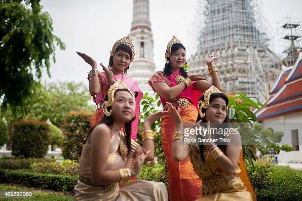 Thai girls pose in traditional dress at Wat Arun during the Songkran water festival on April 13 2015 in Bangkok Thailand The Songkran festival marks...