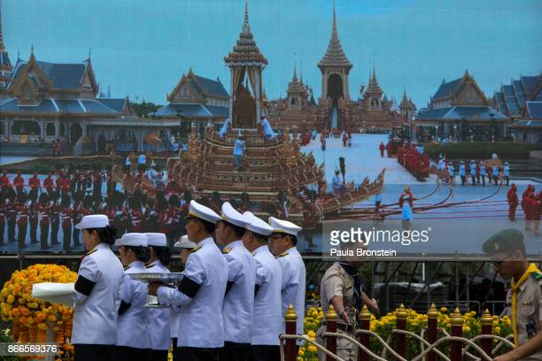 Thai government officials march to a replica of the Royal Crematorium offering flowers ahead of the historical cremation of Thailand's King Bhumibol...