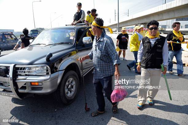 Thai guards of the opposition People's Alliance for Democracy arrive with sticks and golf clubs to help man a checkpoint on the third day of...