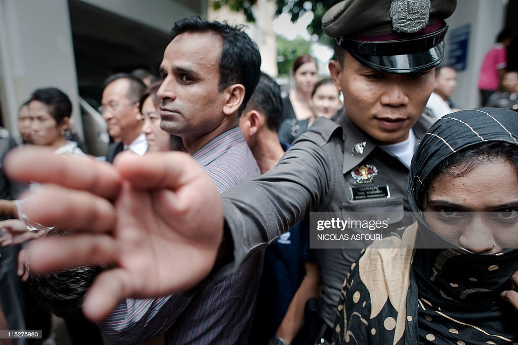 A Thai immigration police officer (C) di : News Photo