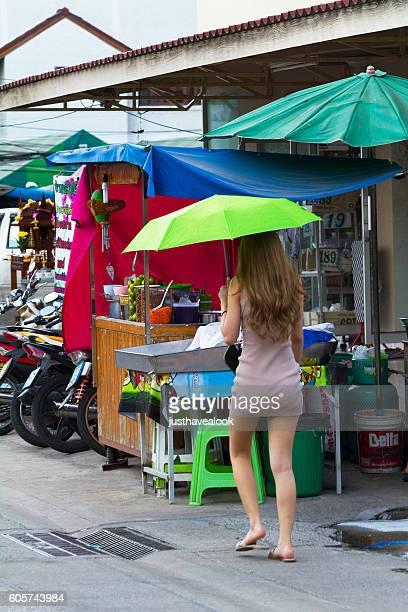 thai kathoey in dress walking with green umbrella - kathoey fotografías e imágenes de stock