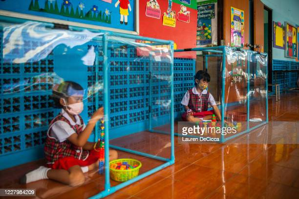 Thai kindergarteners wear face masks as they play in screened in play areas used for social distancing at the Wat Khlong Toey School on August 10,...