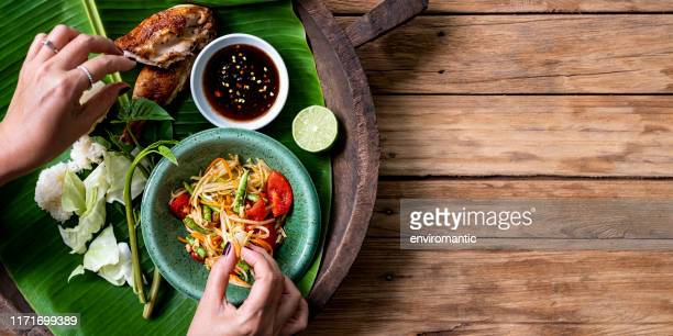 thai lady eating traditionally with her hands, fresh world famous som tam (papaya salad) with bbq chicken, sticky rice and raw salad vegetables on an old wooden table background. - thai food stock pictures, royalty-free photos & images