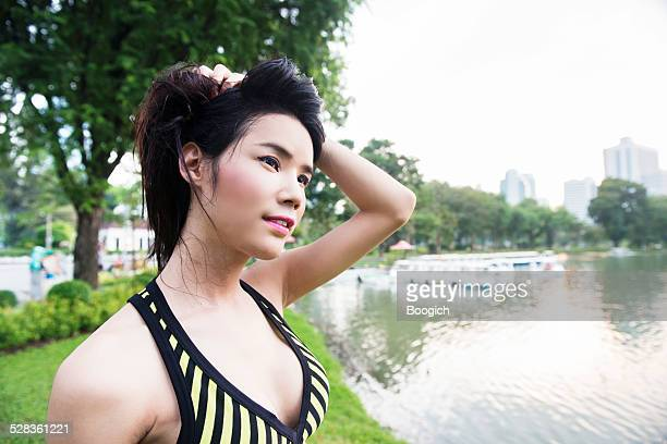 thai ladyboy runner toma descanso en el parque lumpini bangkok - kathoey fotografías e imágenes de stock