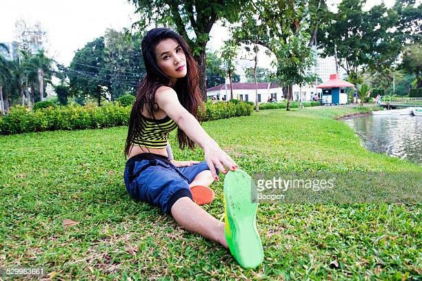 thai ladyboy s'extiende por parque lumpini lago bangkok - kathoey fotografías e imágenes de stock