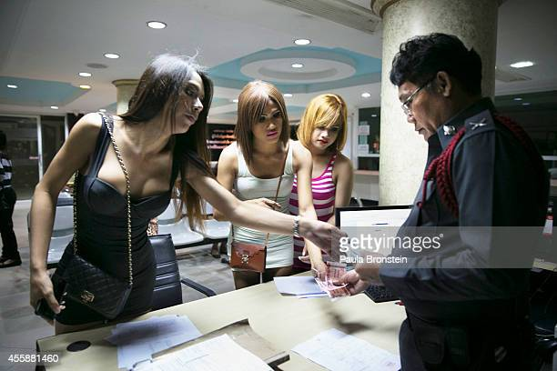 Thai ladyboys pay their fines in a police station September 21 2014 in Pattaya Thailand Pattaya is tackling sex tourism and crime as the city...