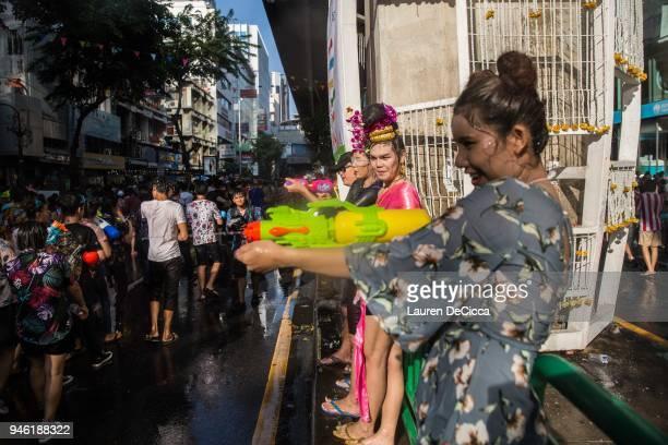 Thai ladyboys spray water guns during the Songkran celebration party on Silom Road on April 14 2018 in Bangkok Thailand Songkran is the Thai new year...