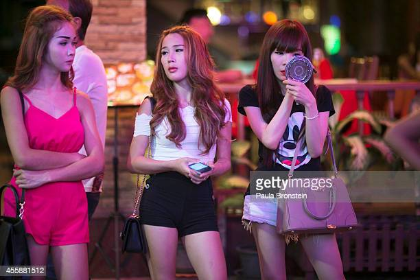 Thai ladyboys wait for customers outside a bar in the red light district September 21 2014 in Pattaya Thailand Pattaya is tackling sex tourism and...