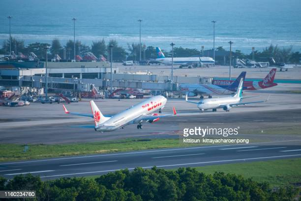 thai lion air taking off at phuket international airport - off stock pictures, royalty-free photos & images
