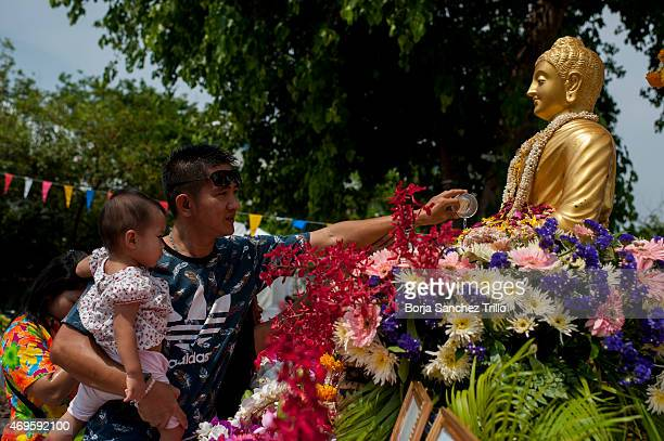 Thai man and his daughter offers prayers at Phra Athit during the Songkran water festival on April 13 2015 in Bangkok Thailand The Songkran festival...