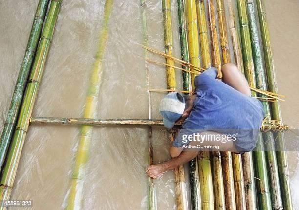 Thai homme bâtiment un radeau de bambou sur la rivière, en Thaïlande